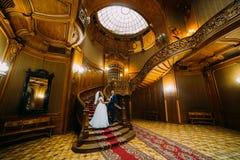 Charmante bruid en het knappe elegante bruidegom stellen op een achtergrond van verbazingwekkend uitstekend binnenland royalty-vrije stock foto