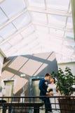 Charmante bruid en knappe bruidegom die aan elkaar met hotelhal als achtergrond kijken Stock Foto's