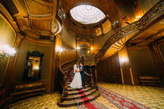 Charmante bruid en knappe elegante bruidegomholding elkaar op een achtergrond van luxueus uitstekend binnenland royalty-vrije stock foto's
