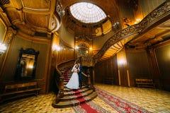 Charmante bruid en knappe elegante bruidegomholding elkaar op een achtergrond van verbazingwekkend uitstekend binnenland stock fotografie