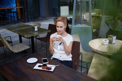 Charmante dame die over iets denken terwijl het genieten van van vrije tijd tijdens ochtendontbijt in comfortabele koffiebar Royalty-vrije Stock Afbeelding