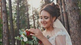 Charmante en gelukkige bruid in een mooie huwelijkskleding met een boeket van bloemen in een pijnboombos in de zon De dag van het stock videobeelden