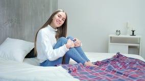 Charmante Europese vrouwenzitting bij bed het glimlachende en stellende bekijken camera stock video