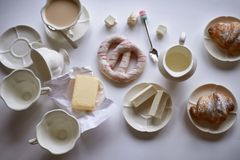 Charmante Franse Ontbijt witte reeks en croissants, boter, heemst, en pretzel Een helder palet stock fotografie