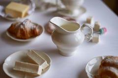 Charmante Franse Ontbijt witte reeks en croissants, boter, heemst, en pretzel Een helder palet stock afbeelding