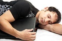 Charmante jonge mensenslaap met in hand laptop Stock Afbeelding