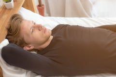 Charmante knappe jonge kerel die iets denken over zijn toekomstig leven op bed bij slaapkamer De aantrekkelijke knappe mens wordt stock fotografie