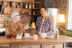 Charmante mens en zijn bejaard vader het drinken sap stock afbeeldingen