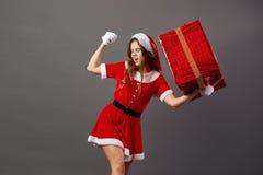 Charmante Mevr. Claus gekleed in de de rode robe, hoed van de Kerstman en de witte handschoenen houdt in haar hand reusachtige aa stock foto