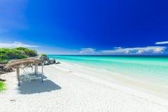Charmante nviting mening van tropisch wit zandstrand en rustige turkooise tedere oceaan op donkere diepe, blauwe hemelachtergrond Royalty-vrije Stock Foto