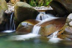 Charmante rustige waterval onder de rotsen van bergkreek stock afbeeldingen