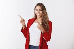 Charmante vriendschappelijk-kijkt vrouwelijke krullend-haired beambte, dragend rood jasje, die verlaten wijsvingersbovenleer rich stock fotografie