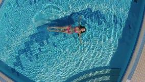 Charmante vrouw die in de blauwe pool zwemmen stock video
