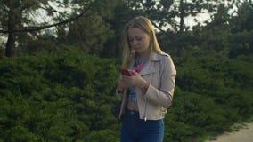 Charmante vrouw die en cellphone in park lopen gebruiken stock video