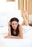 Charmante vrouw die op bed het luisteren muziek ligt Stock Foto's