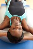 Charmante vrouw die zitten-UPS met een pilatesbal doet Royalty-vrije Stock Foto