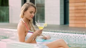 Charmante vrouw het drinken cocktail in pool Portret van vrouwen nippende cocktail stock footage