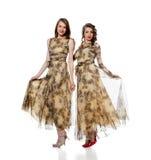 Charmante vrouwen die in kleding van zelfde doek stellen Royalty-vrije Stock Afbeelding