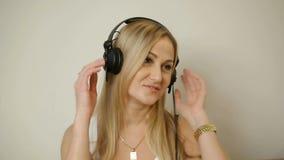 Charmante vrouwenjaren '40 die aan muziek luisteren die hoofdtelefoons dragen stock videobeelden