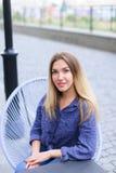 Charmante vrouwenzitting bij koffie buiten en het dragen van blauw overhemd Stock Afbeelding