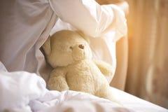 Charmante Witte het Overhemdspyjama's van de Donkerbruine Zittingsslijtage op Bed met Haar Bruin Teddy Bear Stock Afbeeldingen