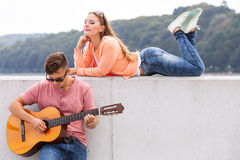 Charmed girl enjoying music. Love romance sound talent passion concept. Charmed girl enjoying music. Young lady listening to men playing guitar Stock Images