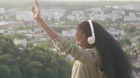 Charmerend Afrikaans Amerikaans meisje luister aan muziek en voelt gelukkig Glimlachend jong zwart meisje op vage stadsachtergron stock footage