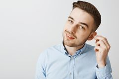 Charmerend Europese mannelijke ondernemer in modieus kapsel die draadloos earbud overhellend hoofd van start gaan die vriend vrag royalty-vrije stock afbeeldingen