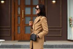 Charmerend geheimzinnige vrouwentribunes buiten, draagt beige laag, leer de zwarte zak, modieuze zonnebril, haar indient zak houd stock foto