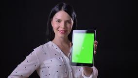 Charmerend jonge donkerbruine vrouw die tablet met chromakey tonen en bij camera, status glimlachen geïsoleerd op zwarte achtergr stock footage
