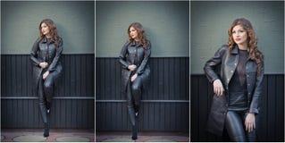 Charmerend jonge donkerbruine vrouw in zwarte leeruitrusting, laag en broeken, met donkergrijze muur op achtergrond schitter Stock Fotografie