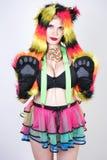 Charmerend plus grootte jonge die vrouw in bonthoed van multicolored vezels met kattenoren en poten wordt gemaakt die in groene b royalty-vrije stock foto