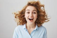Charmerend vrolijk jong Europees wijfje met positieve houding, die ruim glimlachen terwijl het haar op lucht drijft, die zich ove stock afbeelding
