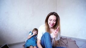 Charmerend vrouwelijke en jonge moeder die op telefoon op achtergrond van babydochter spreken die binnen op vloer in heldere ruim stock video