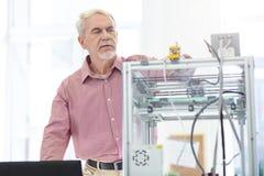 Charmig äldre man som kontrollerar arbete av skrivaren 3D Royaltyfri Fotografi