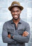 Charmig afrikansk amerikanman som ler med hatten Royaltyfri Foto