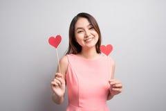 Charmig asiatisk kvinna som rymmer röd hjärtaform Arkivfoton
