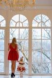 Charmig blond flicka i en röd klänning som rymmer handen av hennes daug royaltyfri bild