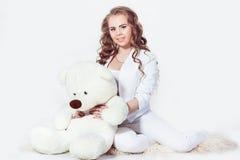 Charmig blond flicka som omfamnar nallebjörnen Royaltyfria Foton