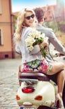 Charmig blond kvinna som rider en sparkcykel med hennes pojkvän Royaltyfria Bilder