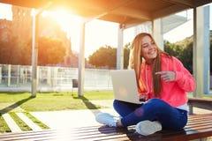 Charmig blond kvinnlig student som pekar för att öppna bärbara datorn Royaltyfri Fotografi