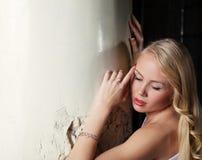 Charmig blond posera lutande kolonn, närbild Royaltyfria Bilder