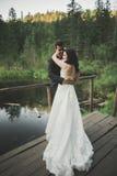 Charmig brud, elegant brudgum på landskap av berg och solnedgång på sjön ursnyggt bröllop för par Royaltyfri Foto