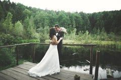 Charmig brud, elegant brudgum på landskap av berg och solnedgång på sjön ursnyggt bröllop för par Arkivfoto