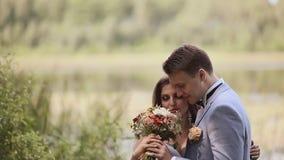 Charmig brud med en bukett och hennes fiance tillsammans på naturen Mjukhet av förbindelse kyss lyckligt tillsammans bröllop lager videofilmer