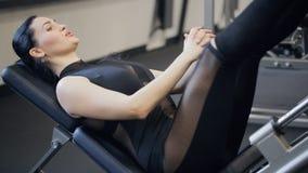 Charmig brunettövningspress lägger benen på ryggen på traineger i idrottshall lager videofilmer