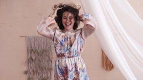 Charmig brunettkvinna i banhoppning för blom- klänning på säng Bristning av hennes hår stock video
