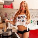 Charmig caucasian kvinna som lagar mat en soppa Arkivbild