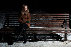 Charmig flicka i förväntan på en bänk fotografering för bildbyråer