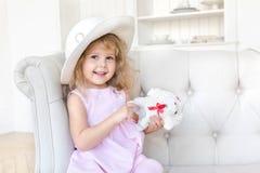 Charmig flicka i klänningen som poserar med leksaken royaltyfri foto